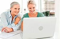 Two businesswomen using laptop in office