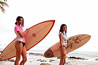Two young women holding surfboards, portrait