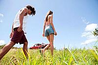 Young couple walking through grass