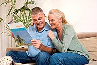 Mature couple with holiday brochure