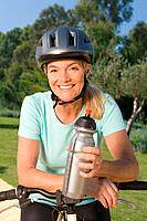 Mature woman cyclist wearing helmet and holding bottle (thumbnail)
