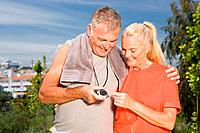 Mature couple looking at stopwatch after workout