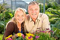 Mature couple with flowers in garden centre (thumbnail)
