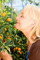 Mature woman smelling fruit tree