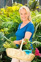 Mature woman amongst plants with basket