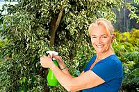 Mature woman spraying plant