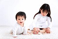 Girl playing with blocks on a rug next to her baby brother