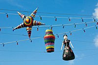 Pinatas hanging on strings of lights against blues sky in Cozumel, Mexico in the Caribbean Sea