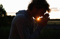 Silhouette of man praying at sunset