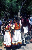 Greek dancers in traditional costume in a crowd. Three women talking. One man.