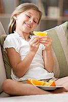 Caucasian girl holding orange slice