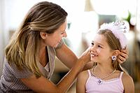 Caucasian mother adjusting tiara on daughter