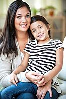 Mixed race girl sitting on mother´s lap