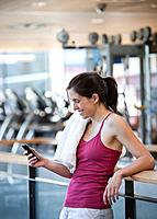 Woman text messaging on cell phone in health club