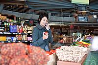 Hispanic woman talking on cell phone and shopping in grocery store