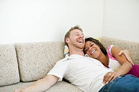 Laughing couple laying on sofa together