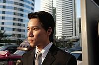 Serious Asian businessman outdoors