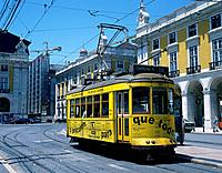 City tram. Yellow colour. Praco de Comercio. Tracks. Overhead cable. Passengers inside. People waiting