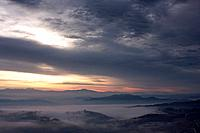 Sunrise over Tiber valley with grey pink and golden sky in the early morning mist of winter