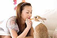 Young woman feeding rabbit, smiling