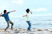 Two young men throwing stones over sea, blurred motion