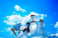 Four snowmen with tools in the snow