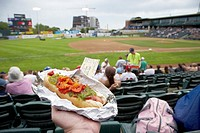 holding hot dog and game ticket sitting in the stand at shaw park baseball stadium formerly canwest home to the winnipeg goldeyes Winnipeg Manitoba Ca...