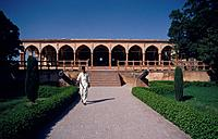 Young man walking through the gardens of Lahore Fort. Buildings. Cannon.