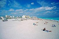 South Miami Beach. Crowded beach. White sand. People. sitting/ lying. White waves. Green sea. Buildings.