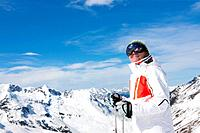 Smiling man wearing ski goggles and holding ski poles on snowy mountain