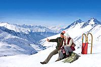 Smiling senior couple with sled sitting and pointing on snowy mountain