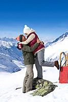 Smiling senior couple hugging face to face on snowy mountain