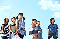 School children standing under sky, looking away, copy space