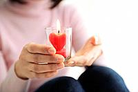 Woman holding heart shaped candle