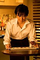Waiter carrying a plate of food to a table