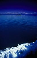 Great Barrier Reef. Shadows of people in wash from cruise ship. Tiny coral cay/ island in distance. Low Isles.