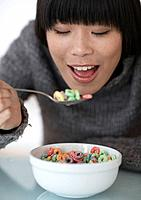 Mid_Adult Woman Eating Breakfast Cereals