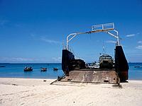 Stone Town. Dar_Es_Salaam car ferry. Stern plate down for loading. Battered truck. Boats. Sea.