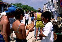 A group of people shopping at market stalls in a holiday resort by the coast. Tourists purchasing local crafts as souvenirs.