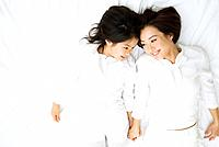 Mother and daughter lying down on white sheet