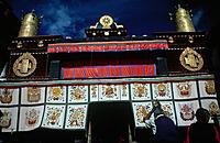 Sacred Jokhang site. Tsuglagkhang temple complex. Decorated entrance/ Khyamra Gochor. Dark sky. Person.