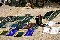 Mud banks. Person laying out saris/ sarongs to dry in sun. Patterns/ blue/ green colours.