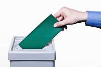 A man putting a blank green ballot into a ballot box, close_up hands