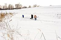 Children clear snow from a frozen pond on a farm near Dunbar, NE.