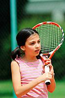 Young Girl Holding Racket And Looking Away