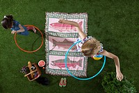 A mother and daughter using hula hoops at a picnic in the park, overhead view