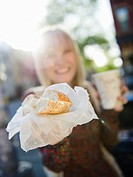 USA, Brooklyn, Williamsburg, Woman showing bagel