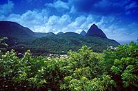 Town on coast. Woods. Les Pitons rock formations. Deep blue sky.