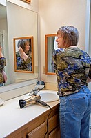 This middle aged Caucasian woman is fixing her hair after blow drying it in the bathroom, looking in a mirror  An everday grooming moment lifestyle st...
