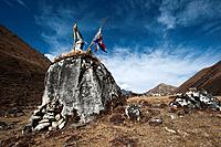Prayer flags on top of a cairn on the Laya_Gasa trek in Bhutan
